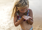 Little girl on the beach with an elver on her hand - MGOF000721