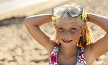 Portrait of smiling blond little girl with diving mask and hands behind her head on the beach - MGOF000731