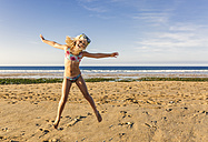 Spain, Colunga, little girl with diving mask jumping in the air on the beach - MGOF000733