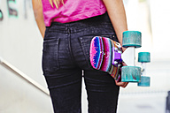 Young girl holding a colorful skateboard - GEMF000368