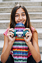 Portrait of smiling teenage girl with colorful skateboard sitting on stairs - GEMF000375