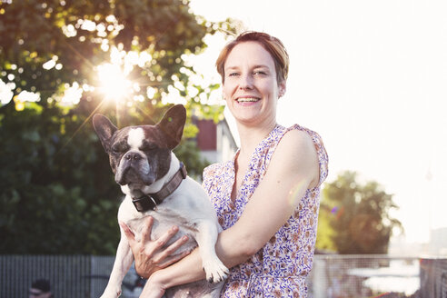 Portrait of smiling woman holding French bulldog - TAM000306
