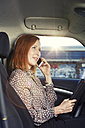 Redheaded businesswoman sitting in her car telephoning with smartphone - TAM000307