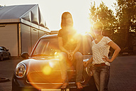Two women in front of their car at backlight - TAM000315