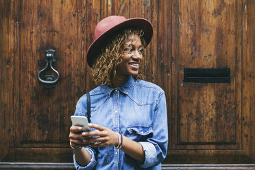 Spain, Barcelona, portrait of smiling young woman with smartphone  standing in front of wooden door - EBSF000914