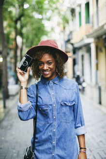Spain, Barcelona, portrait of smiling young woman wearing hat and denim shirt holding camera - EBSF000917