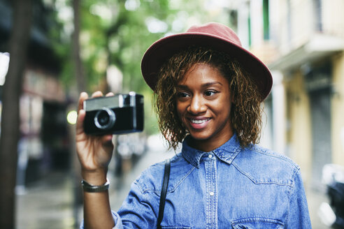 Portrait of smiling young woman wearing hat and denim shirt holding camera - EBSF000919