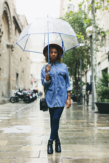 Spain, Barcelona, portrait of young woman with umbrella wearing hat and denim shirt - EBSF000925