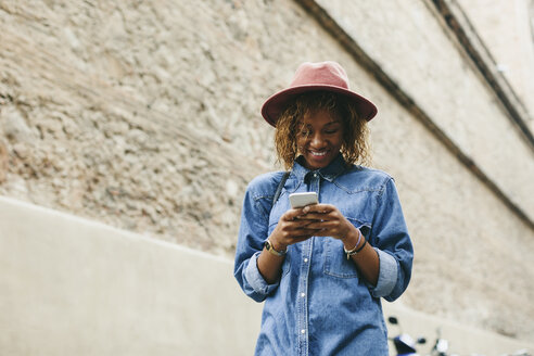 Portrait of smiling young woman wearing hat and denim shirt looking at smartphone - EBSF000929