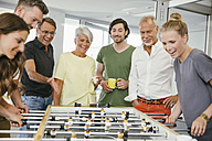 Office colleagues playing foosball during break - MFF002214