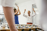 Office colleagues playing foosball during break - MFF002224