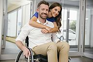 Man in wheelchair with his girlfriend, embracing happily - MFF002227