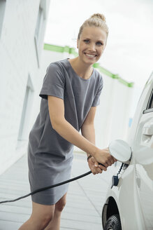 Young woman charging electric car - MFF002221