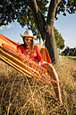Smiling woman wearing hat relaxing in a hammock with digital tablet - UUF005653