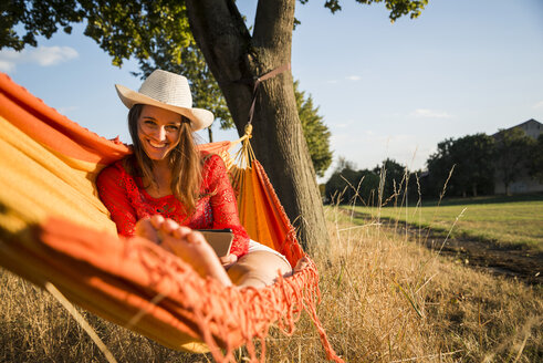 Portrait of smiling woman wearing hat relaxing in a hammock with digital tablet - UUF005655