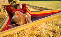 Feet of woman relaxing in a hammock - UUF005658