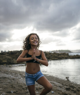 Spain, Gijon, portrait of smiling little girl on a beach - MGOF000750