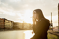 Germany, Muenster, young woman smoking cigarette in front of city harbour - TAM000299