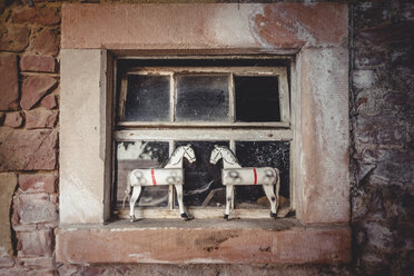 Two vintage toy horses in an old barn on a window sill - IPF000245