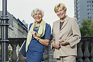 Germany, Berlin, portrait of two smiling senior businesswomen with laptop and smartphone - TAM000322