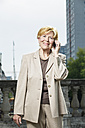 Germany, Berlin, portrait of smiling senior businesswoman telephoning with smartphone - TAM000325