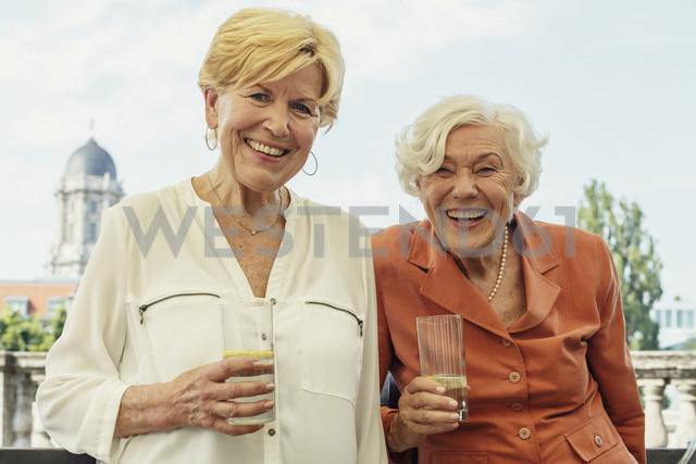 Germany, Berlin, portrait of two smiling senior women with glasses of mineral water - TAMF000329 - A. Tamboly/Westend61