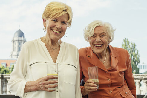 Germany, Berlin, portrait of two smiling senior women with glasses of mineral water - TAMF000329