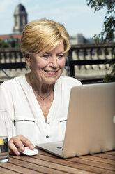 Germany, Berlin, portrait of smiling senior woman using laptop - TAMF000332