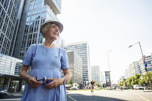 Germany, Berlin, portrait of smiling senior woman watching something - TAMF000343