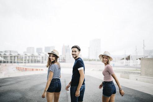 Spain, Barcelona, portrait of three friends looking over their shoulders - JRFF000076
