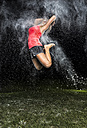 Young woman jumping in the air in flour dust cloud - STSF000922