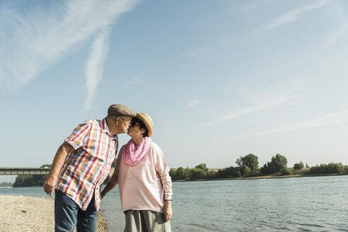 Germany, Ludwigshafen, kissing senior couple at riverside - UUF005669