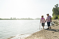Germany, Ludwigshafen, senior couple walking hand in hand at riverside - UUF005708