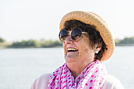 Portrait of smiling senior woman wearing sunglasses and summer hat - UUF005709