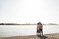 Germany, Ludwigshafen, kissing senior couple standing at riverside - UUF005712