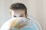 Little boy hiding behind a globe - DEGF000549