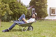 Smiling man lying in wheelbarrow in garden - RBF003201