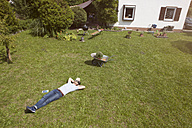Man lying on lawn relaxing from gardening - RBF003202