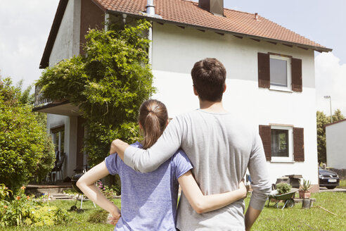 Couple in garden looking at residential house - RBF003170