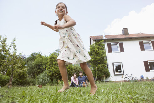 Playful girl with parents in garden - RBF003210