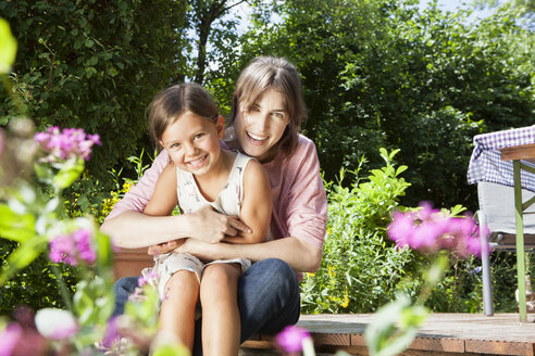 Happy mother and daughter in garden - RBF003229