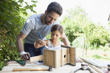 Father and daughter painting a birdhouse - RBF003232