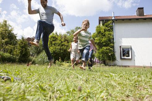 Carefree family running in garden - RBF003238