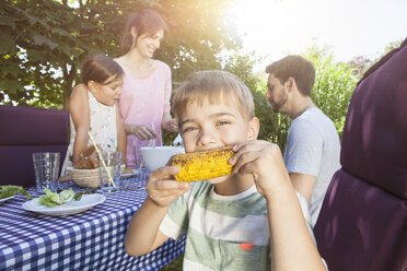 Boy eating a corn cob on a family barbecue in garden - RBF003251