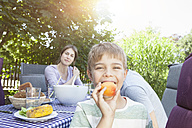 Smiling boy with his family holding a fruit at garden table - RBF003186