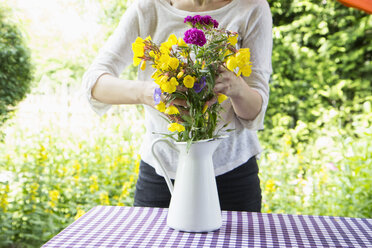 Woman arranging bunch of flowers on garden table - RBF003187