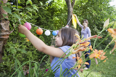 Mother and daughter hanging up a garland in garden - RBF003190