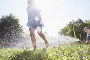 Boy and girl splashing with water in garden - RBF003254