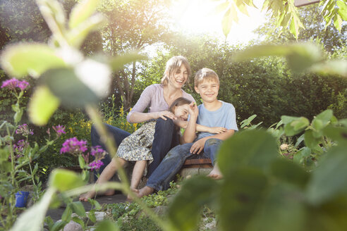 Happy mother, son and daughter in garden - RBF003257