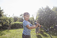 Boy and girl splashing with water in garden - RBF003260